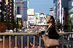 Caucasian woman downtown Tokyo at night, Tokyo, Japan