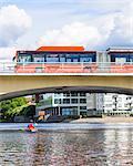 Man kayaking under bridge