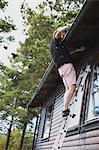 Man on ladder repairing roof