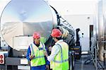 Workers talking by tanker truck