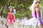 Girls wearing fairy costumes in backyard