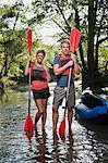 Couple holding kayak paddles in creek
