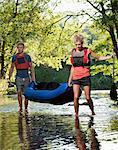 Couple carrying kayak in creek