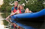 Couple relaxing in kayak in creek