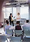 Businesswomen talking, leading conference presentation