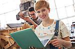 Portrait smiling female designer using laptop in workshop