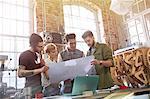 Designers examining blueprints in workshop