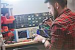 Male engineer assembling electronics, using soldering iron