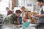 Designers brainstorming at laptop in workshop