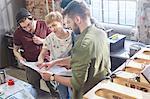 Designers meeting, reviewing plans in workshop