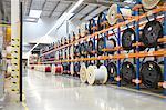 Large spools on racks in fiber optics factory