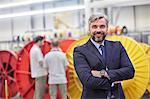 Portrait smiling, confident businessman in fiber optics factory