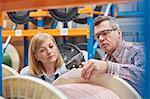Male and female supervisors using IR code scanner, scanning spool in fiber optic warehouse