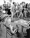 1960s LONG BLONDE HAIR WOMAN SITTING WATCHING GROUP OF YOUNG SPRING BREAK TEENS DANCING WEARING BEACH BATHING SUITS SEASIDE