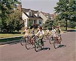 1960s 1970s GROUP OF 7 CHILDREN RIDING BIKES DOWN SUBURBAN STREET