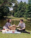 1960s COUPLE PICNIC MAN WOMAN FOOD POND PICNICS EAT MEN WOMEN BASKET OUTDOOR OUTSIDE GRASS