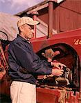 1960s MAN FARMER REPAIRING TRACTOR FARM EQUIPMENT MACHINERY