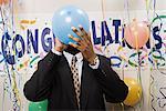 Businessman blowing up a balloon