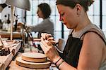 Female jeweller using wire brush workbench