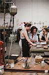 Three female jewellers looking at digital tablet at workbench meeting