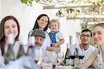 Family having lunch outdoors under grapevine trellis