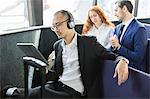 Businessman listening to headphones looking at digital tablet on passenger ferry