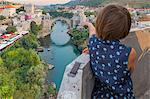Young girl on the minaret of Koski Mehmed Pasha mosque looking the Old Bridge (Stari Most), Mostar, Bosnia and Herzegovina