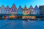 Blue lights of dusk on the colorful medieval houses in Market Square Bruges West Flanders Belgium Europe