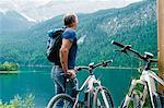 Senior man, standing beside bicycle, looking at view, Elbsee, Bavaria, Germany