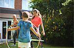 Boy watching mother and teenage sister hoola hooping in garden