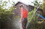 Girl standing on garden sprinkler