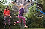 Girls jumping over garden sprinkler