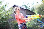 Teenage girl squirting water gun in garden