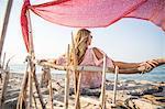 Rear view of woman sitting on beach relaxing, Palma de Mallorca, Islas Baleares, Spain, Europe