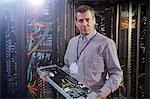 Portrait male IT technician holding panel in server room