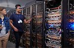 IT technicians walking along panels in server room