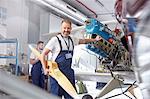 Portrait confident male engineer mechanic working on airplane in hangar