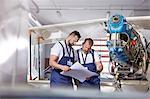 Male engineer mechanics examining plans, fixing airplane in hangar