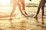 Young friends splashing in sunny summer ocean surf