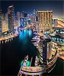 Cityscape of Dubai, United Arab Emirates at dusk, with illuminated skyscrapers lining the Dubai Creek.