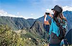 Woman takes a picture on her smartphone of Machu Picchu on the Inca Trail, Cusco, Peru