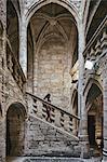 Female tourist and baby moving down church stairway, Pezenas, Occitanie region, France