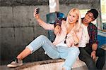 Young skateboarding couple sitting on ramp taking smartphone selfie
