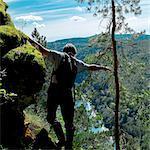 Man hiking, balancing on rocks, rear view, Ural, Sverdlovsk, Russia, Europe