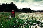 Woman standing in meadow, rear view, Ural, Sverdlovsk, Russia, Europe