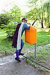 Mature superhero putting hands in orange garbage bin