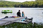 Two girls sitting on jetty beside lake, rear view