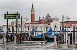 Italy, Veneto, Venice. Gondolas and view of San Giorgio Maggiore Isle from Palazzo Ducale Pier.