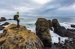 A man admires the ocean and its rocks near Arnarstapi, Snaefellsnes peninsula, Western Iceland, Europe.