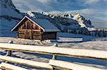 Wooden lodge and fence covered in snow. Passo delle Erbe, Bolzano, Trentino Alto Adige - Sudtirol, Italy, Europe.